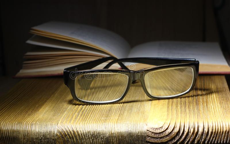 Soft focus retro style books and glasses on a dark background. The concept of reading and education. Soft focus retro style books stock image