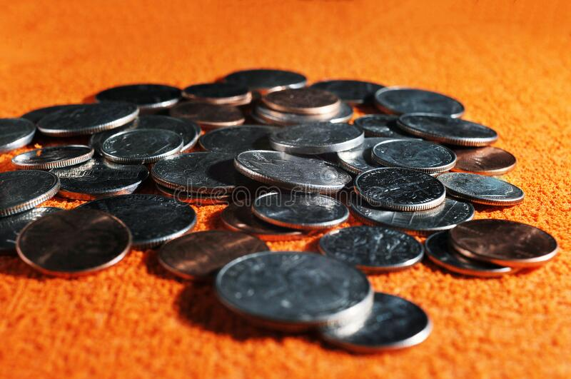 Scattered silver and golden united states coins on orange fabric textured background. Soft focus of scattered silver and golden united states coins on orange stock photo