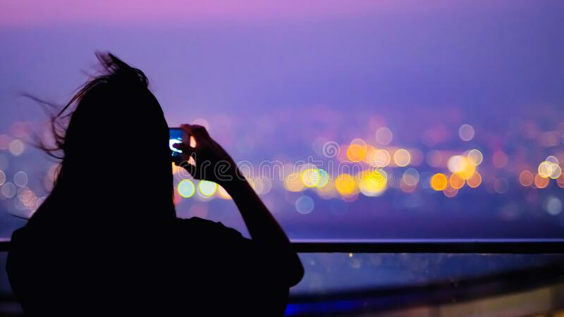 Soft focus and Silhouette of young woman with long hair to take a photo cityscape on top of building with city colourful bokeh lig. Soft focus and Silhouette of stock photo