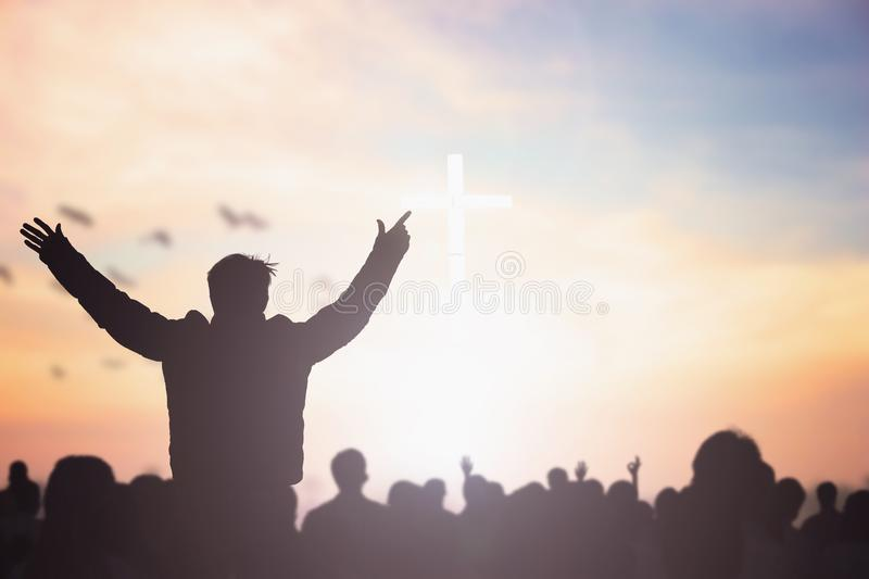 Praise and worship concept: Silhouette human raising hands to praying God on blurred cross with crown of throne sunset background stock images