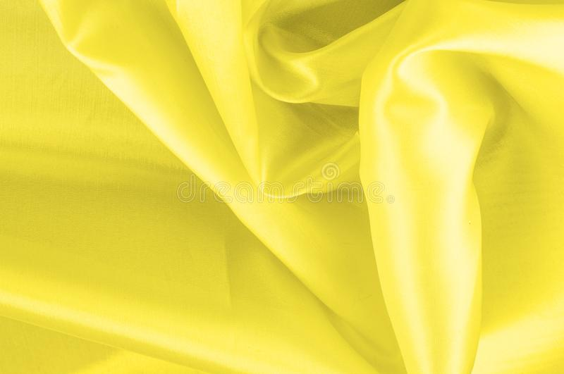 Soft focus. texture, pattern. fabric silky yellow, solar Golden. Yellow silk feil. Like the body to the taffeta, it has a smooth arm that creates a subtle sheen stock images