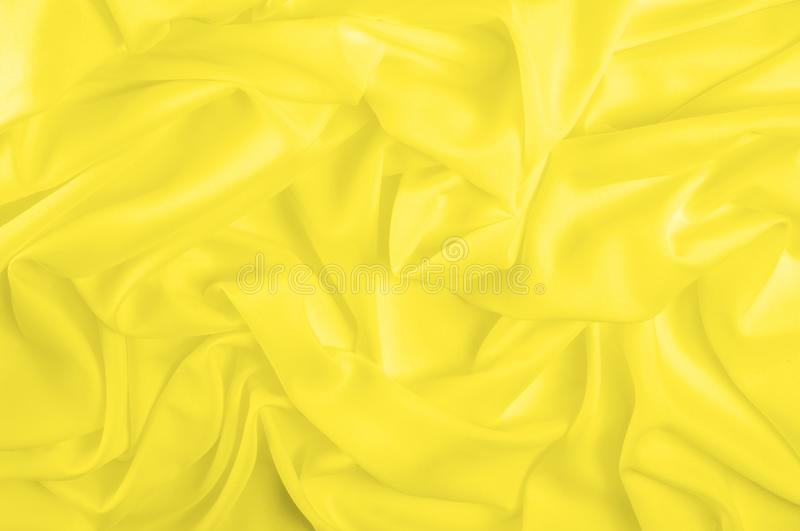 Soft focus. texture, pattern. fabric silky yellow, solar Golden. Yellow silk feil. Like the body to the taffeta, it has a smooth arm that creates a subtle sheen stock photos