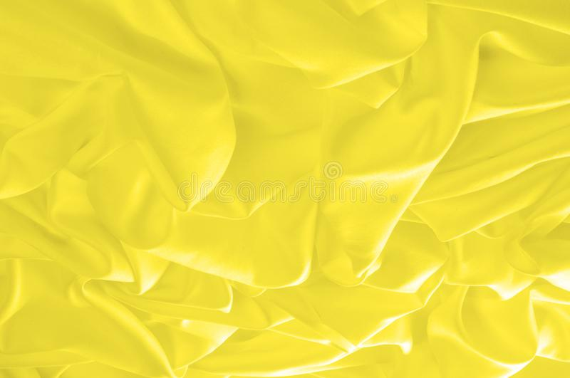 Soft focus. texture, pattern. fabric silky yellow, solar Golden. Yellow silk feil. Like the body to the taffeta, it has a smooth arm that creates a subtle sheen royalty free stock photography