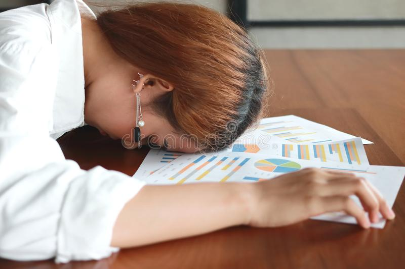 Soft focus of tired overworked young business woman bend down head on charts in office stock photography