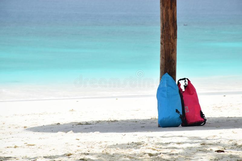 Soft Focus to Blue and Pink Waterproof bag are under the shadow of the umbrella while waiting. For the rain to stop royalty free stock image