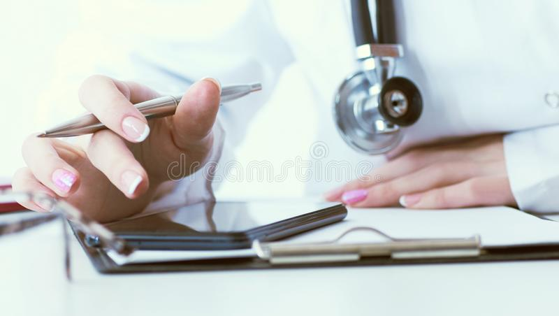 Soft focus of woman doctor touching screen on modern smart phone during the consultation in the workplace hospital. Close-up of female doctor hands touching royalty free stock image