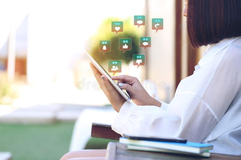 Soft focus of Woman hand holding tablet smart device with hologram or icon of set of social media and communication technology co. Ncept royalty free stock image