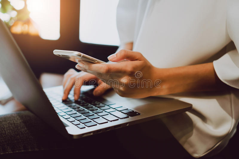 Soft focus of woman hand working with phone on desk in coffee shop. Vintage tone. royalty free stock photo