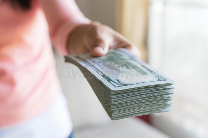 Soft focus on woman hands proposing money us dollar bills. To you royalty free stock photo