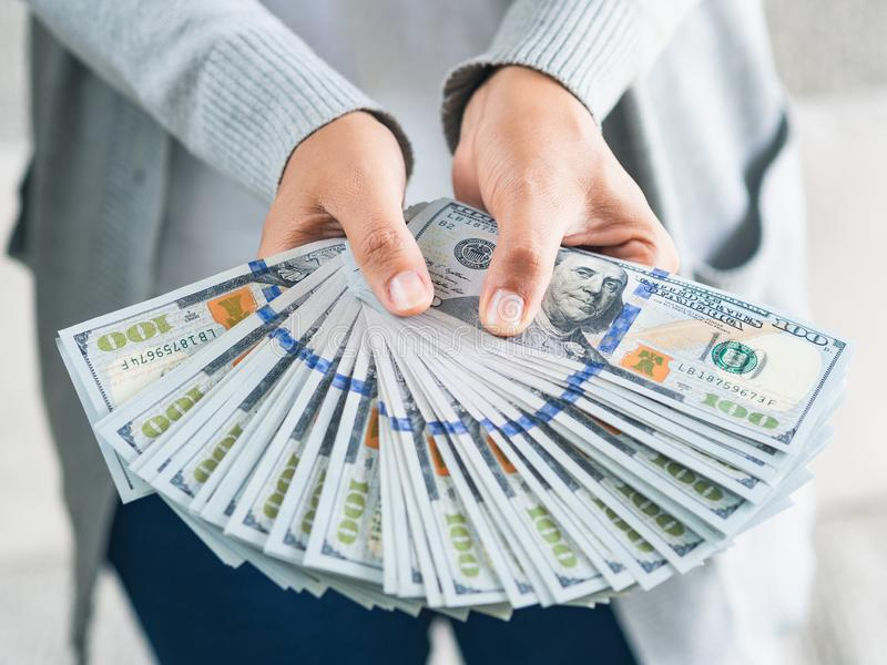 Soft focus on woman hands proposing money us dollar bills to you.  stock image