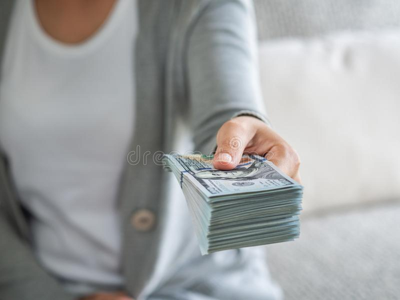 Soft focus on woman hands proposing money us dollar bills to you.  stock images