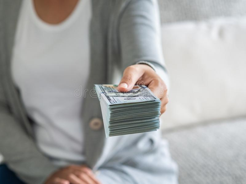 Soft focus on woman hands proposing money us dollar bills to you.  royalty free stock photo