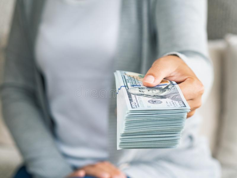 Soft focus on woman hands proposing money us dollar bills to you.  royalty free stock photos