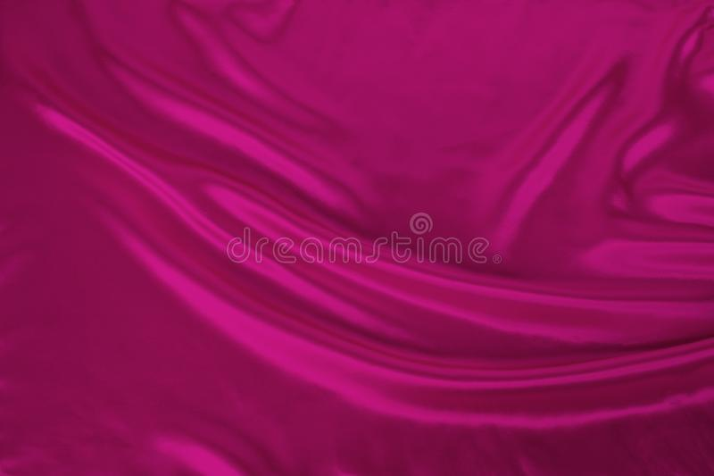 Soft folds on bright pink shiny silk, luxury concept, background for the designer, horizontal, close-up, copy space royalty free stock image
