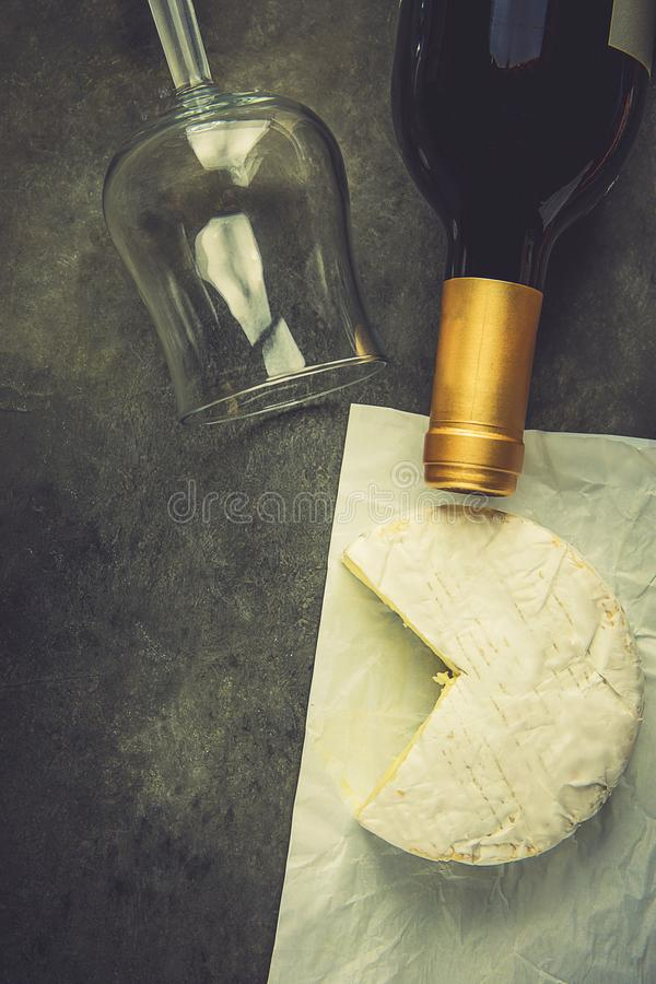 Soft French Camambert Cheese with Cut out Wedge on White Parchment Paper Empty Glass Wine Bottle on Dark Stone Background royalty free stock image