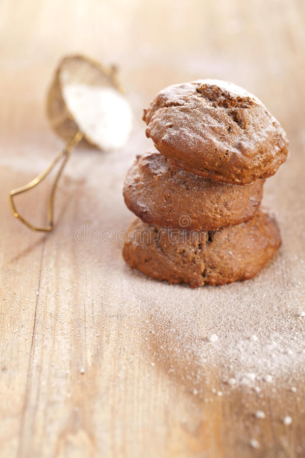 Soft ginger cookies three stacked and dusted. On wooden table, sieve with caster sugar on background, shallow dof stock photos