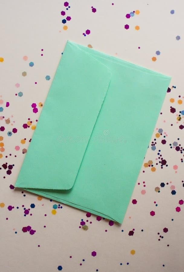 Green envelop on light festive background. Soft green envelop on light festive background with sparkles. Flat lay style stock image