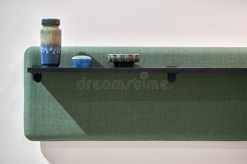 Soft green panel with dark shelf on light wall royalty free stock images