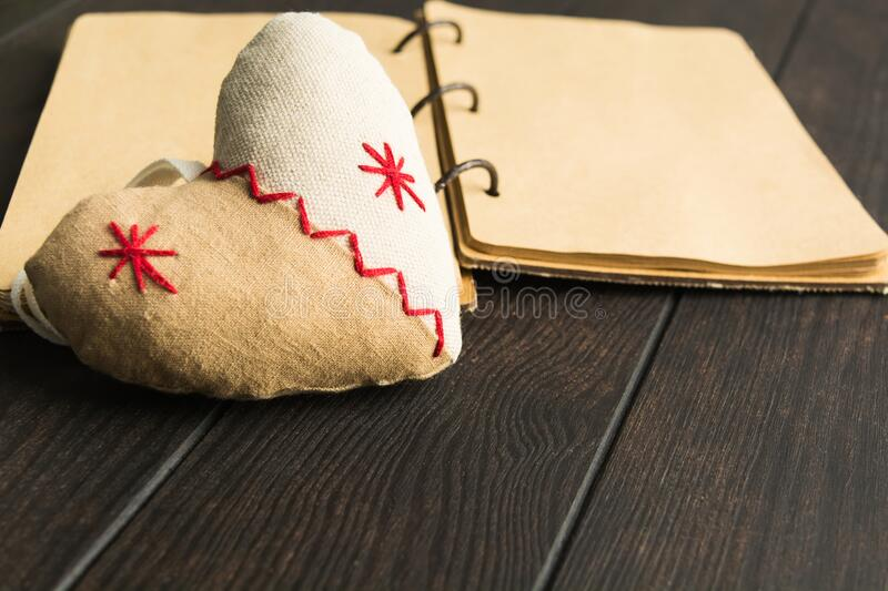 Soft heart made from textile with open notebook on background over brown wooden table with copy space stock photos