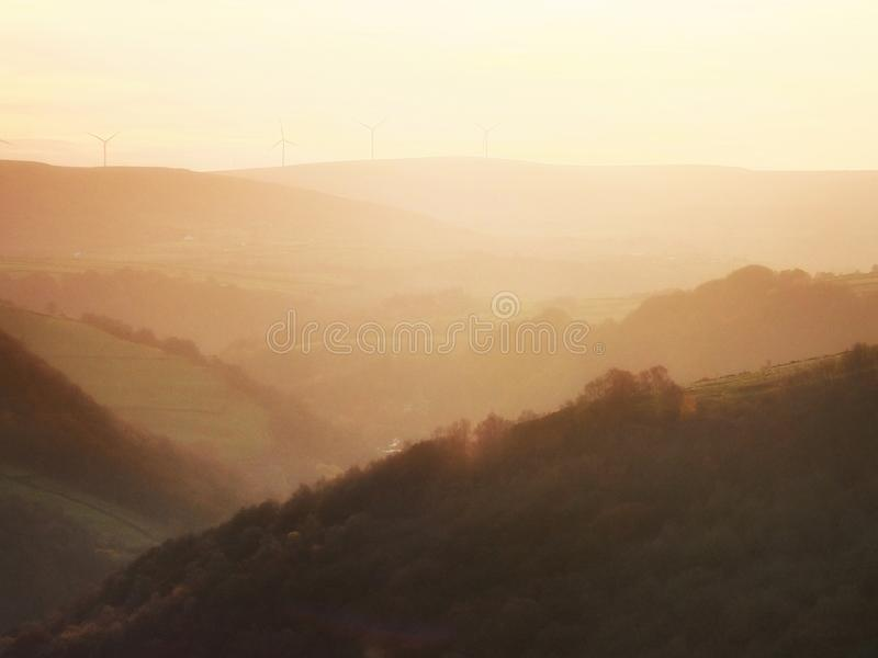 Soft hillside tree covered valley landscape blurred by fog at sunrise glowing a warm orange color with the tops of hills. A soft hillside tree covered valley royalty free stock image