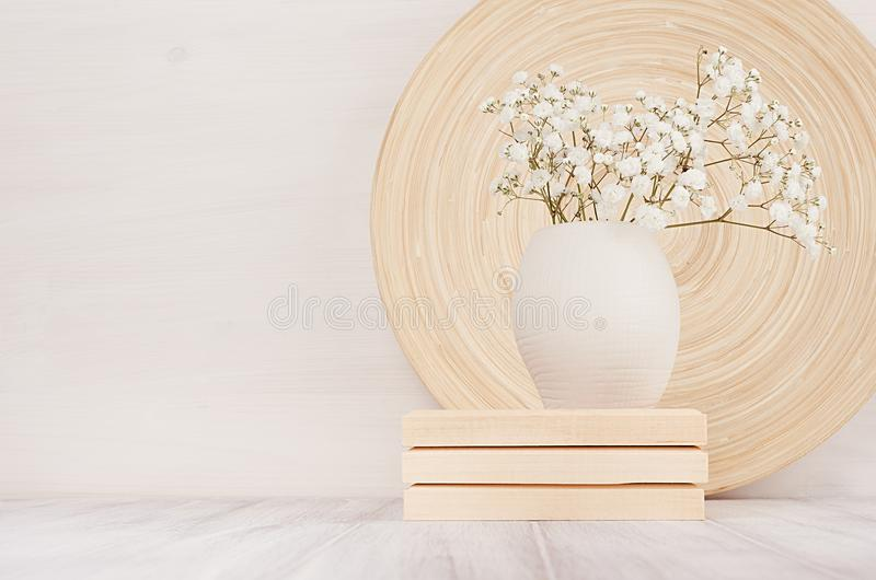 Soft home decor of beige bamboo dish and white small flowers in ceramic vase on white wood background. royalty free stock images