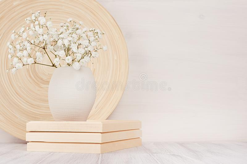 Soft home decor of beige bamboo dish and white small flowers in ceramic vase on white wood background. Interior. royalty free stock image