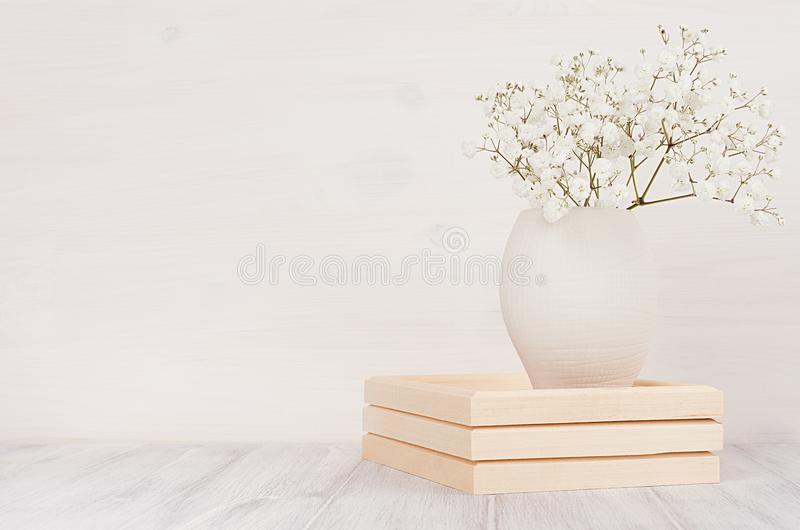 Soft home decor of white small flowers in ceramic vase on white wood background. royalty free stock image