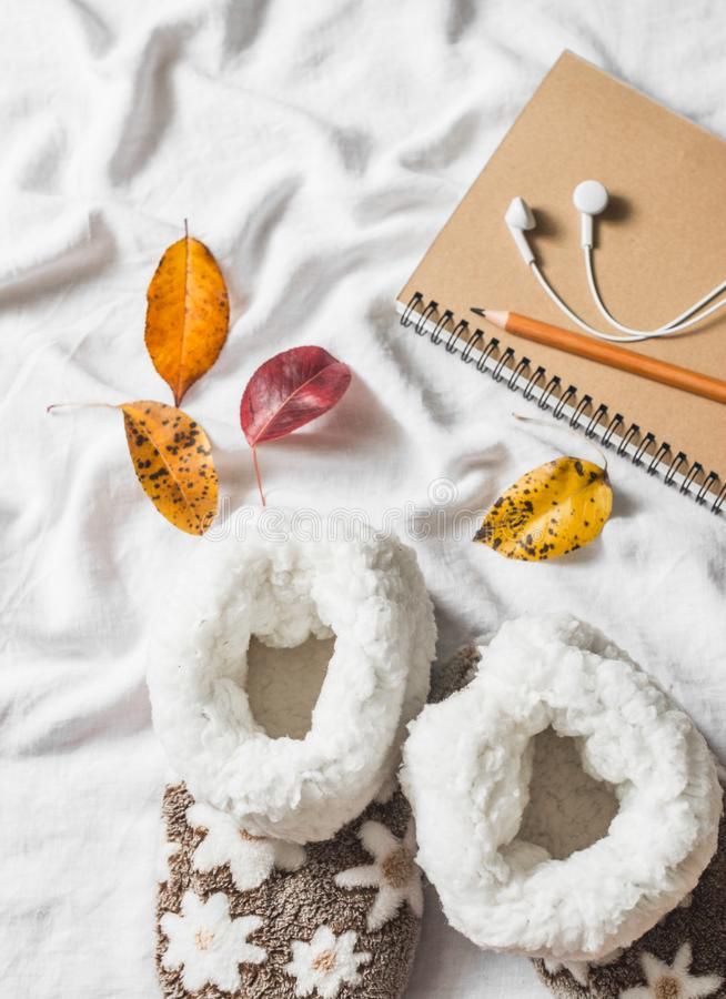 Soft home uggs, notepad, headphones, autumn leaves - lazy cozy home weekend. On a light background royalty free stock photos
