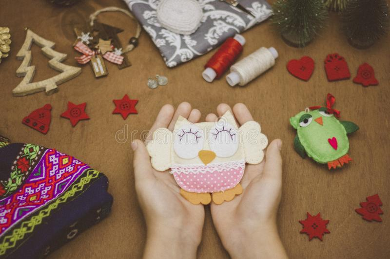 Soft homemade toy holding the child`s hands on the table with sewing and Christmas decorations.  stock images