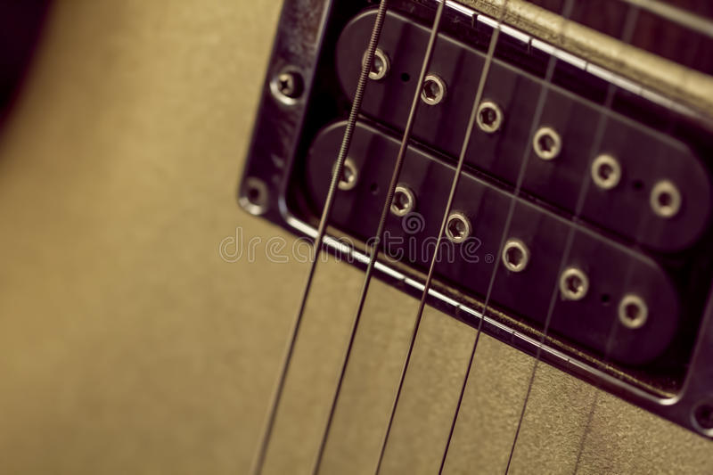 Soft image of a black humbucking pickup on a gold guitar. Nice background or poster image for a rock, blues, or jazz music club, with copy space stock photography