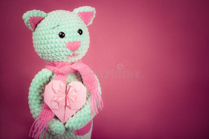 Soft knitted cat and valentine card on pink background. Soft knitted toy. Romantic gift. Copy space stock photos