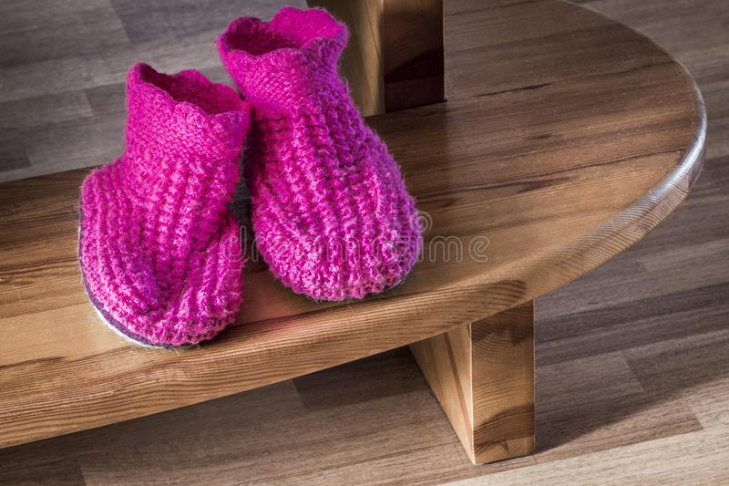 Soft knitted slippers. Purple soft knitted slippers lay on the step royalty free stock photography