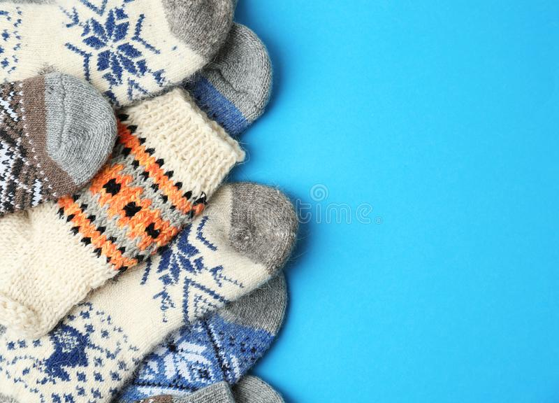 Soft knitted socks on light blue background, space for text. Winter clothes. Soft knitted socks on light blue background, flat lay with space for text. Winter stock image