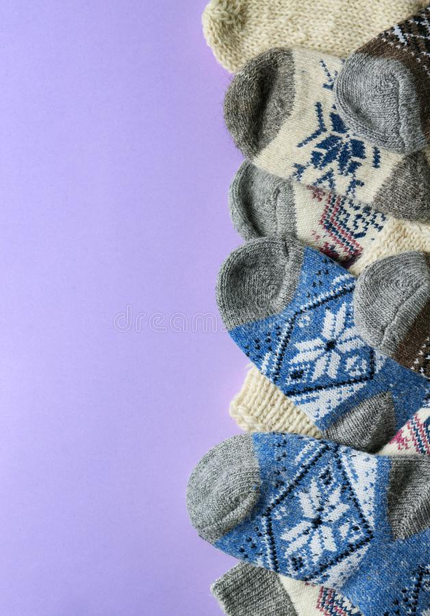 Soft knitted socks on violet background, space for text. Winter clothes. Soft knitted socks on violet background, flat lay with space for text. Winter clothes stock photos