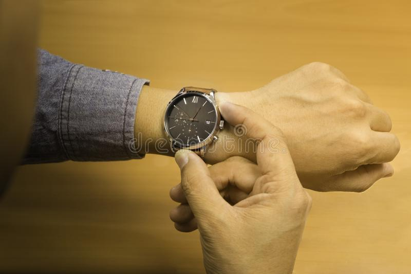 Soft light, Men`s looking at his luxury watches brown leather strap that are worn in the hands,  to checking or setting the time royalty free stock image