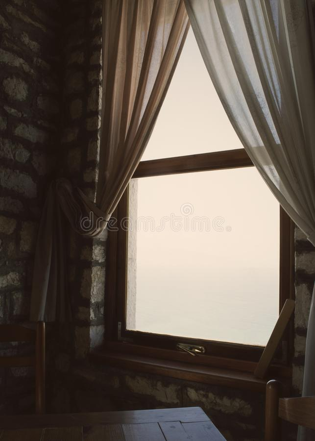 Soft light seeping in from a window. Soft light seeping in from a window partly covered by thin curtains. Chairs and a table in front of the window royalty free stock images