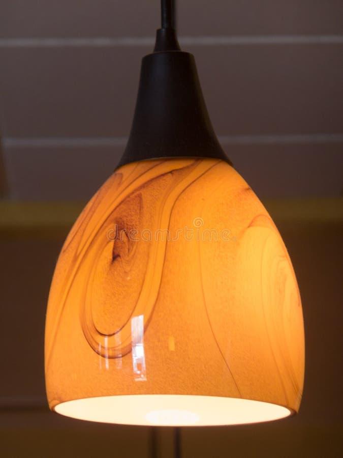 Soft Lighting. Hanging globed lamp fixture with orangish brown swirls stock images