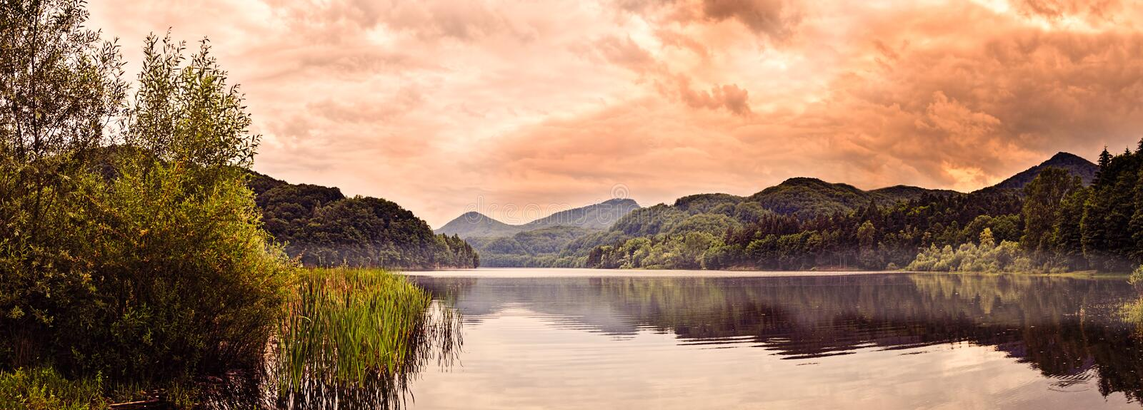 Soft Mist Over Lake. Panoramic view of a lake with soft mist over the water and dramatic sky (romantic interpretation stock photography