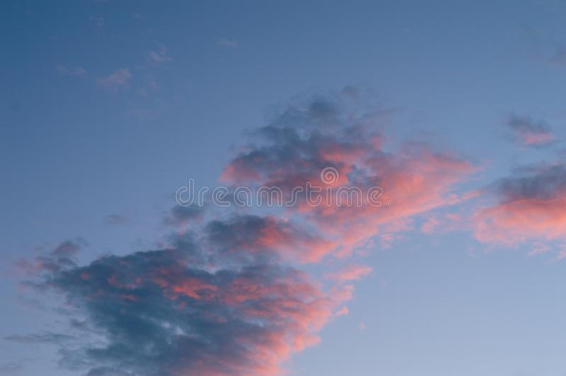 Soft pastel blue sky with pink clouds stock photos