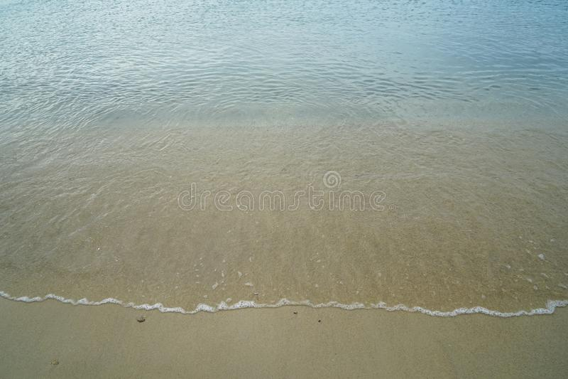 Soft pastel clean sandy beach with fresh clear sea water and white foamy wave line background and copyspace on Ornos shore. Mykonos, Greece stock images