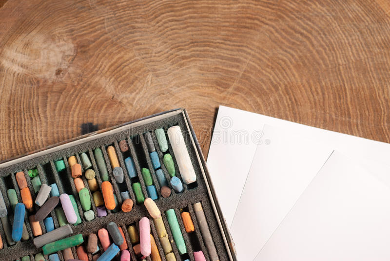 Soft pastels for artists and drawing paper. On the wooden table royalty free stock photo