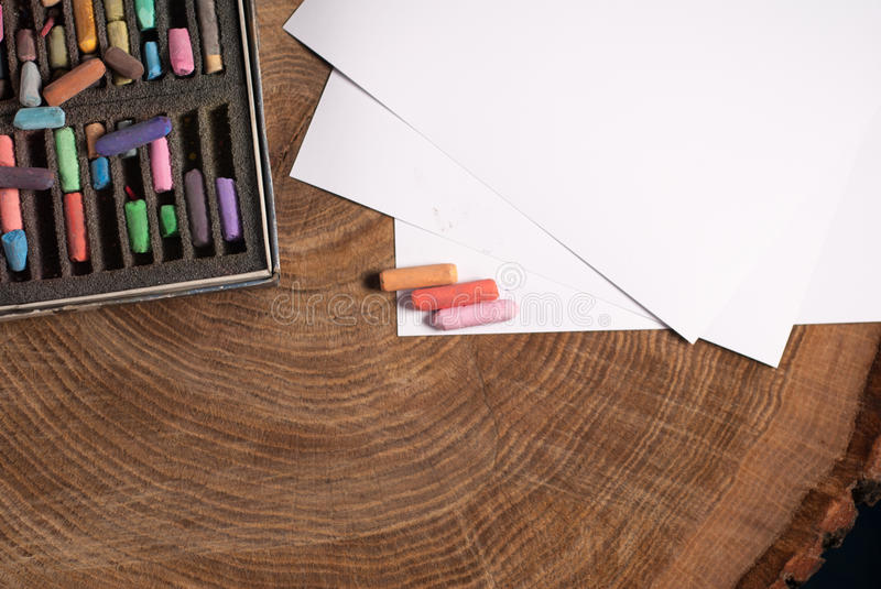 Soft pastels for artists and drawing paper. On the wooden table royalty free stock images