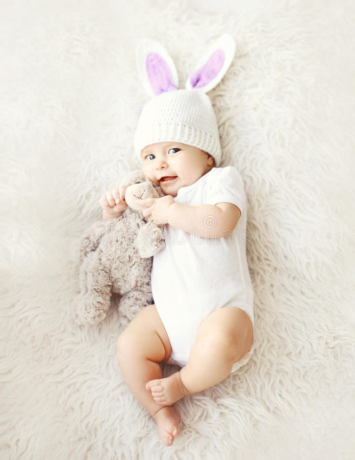 Soft photo of sweet cute baby in knitted hat with a rabbit ears. And teddy bear lying on the bed, top view stock photography