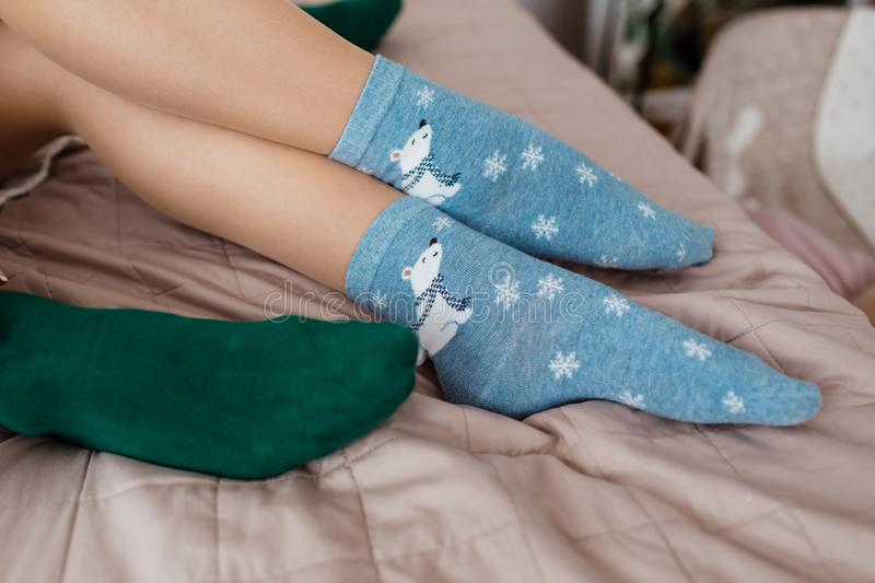 Soft photo of woman and man on the bed. Female and male legs of couple in warm socks. Christmas, love, lifestyle concept.  royalty free stock photo