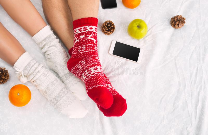 Soft photo of woman and man on the bed with phone and fruits, top view point. Female and male legs in warm woolen socks royalty free stock image