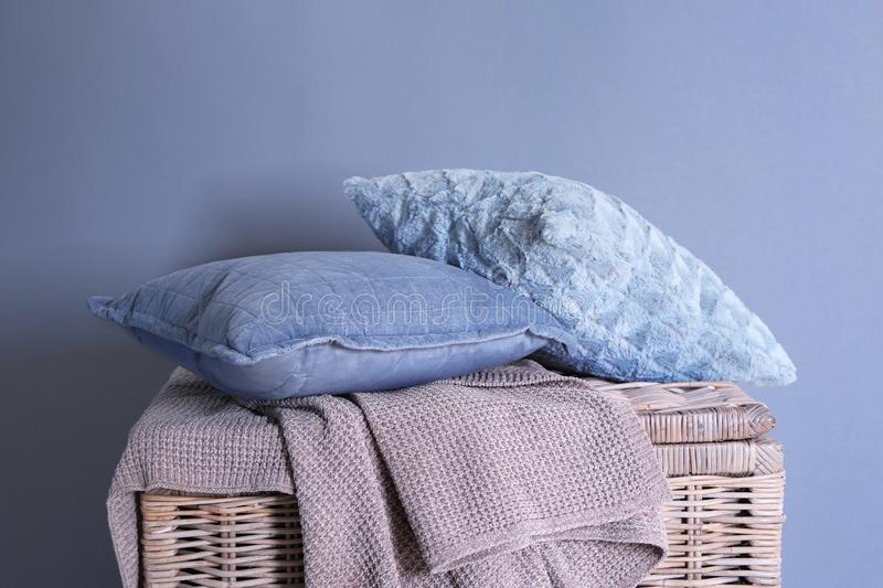 Soft pillows with plaid on wicker basket near grey wall stock images