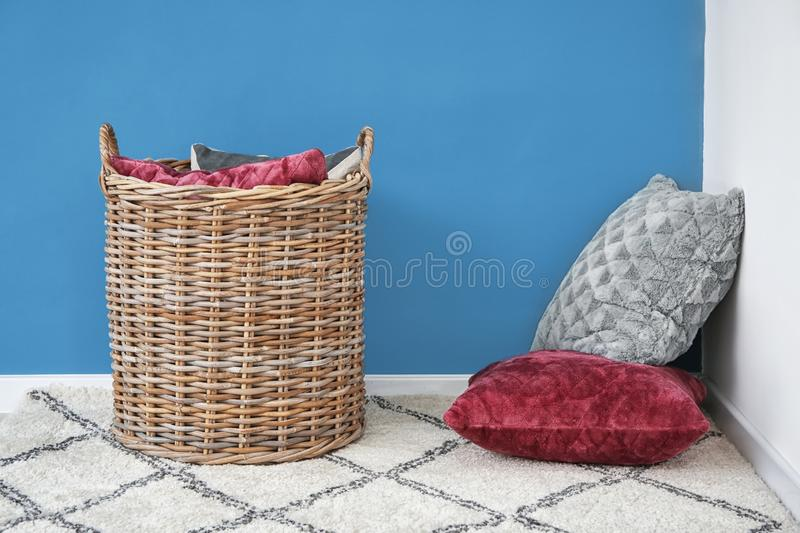 Soft pillows with wicker basket on carpet near color wall indoors royalty free stock images