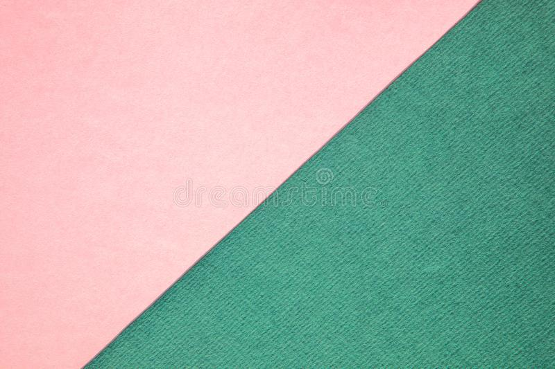 Soft pink and green abstract duo tone background design. Textured and plain paper sheets divided diagonaliy creating line partition. Trendy soft pink and green royalty free stock images