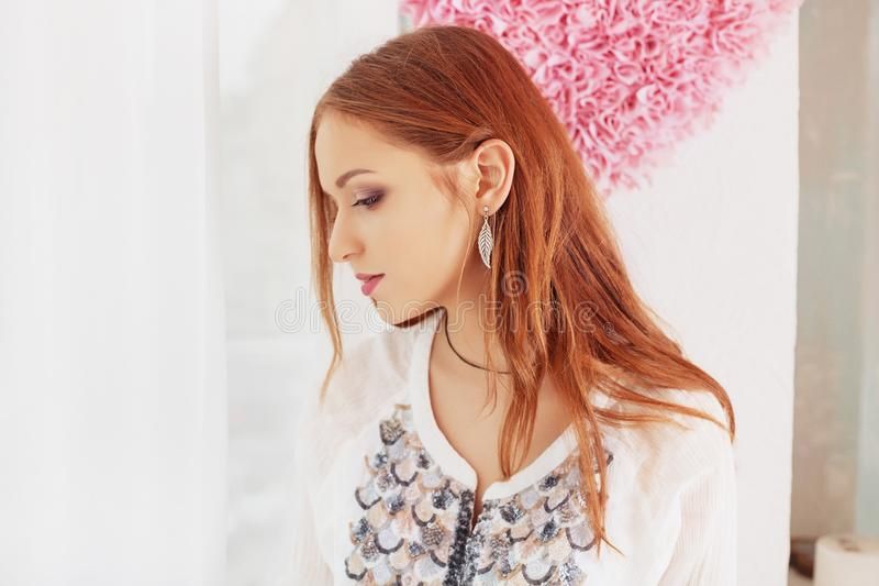 Soft red-haired girl looking out the window. The concept of home royalty free stock image