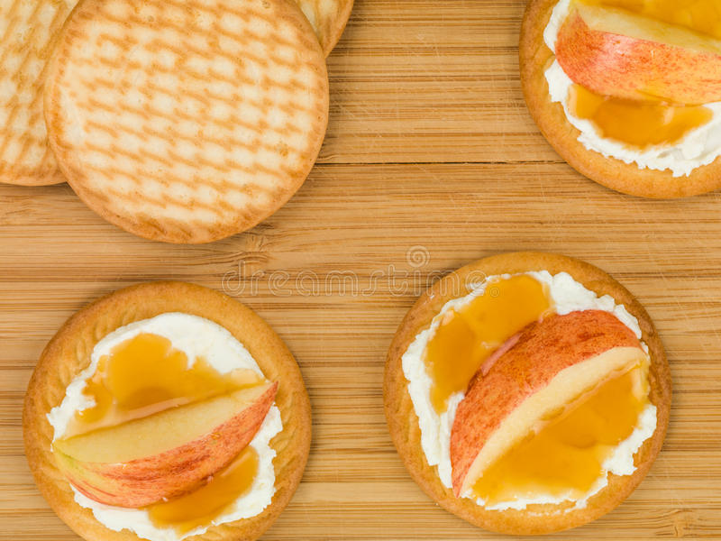 Soft Ricotta Cheese With Sliced Apple and Honey on a Biscuit or Cracker royalty free stock photography